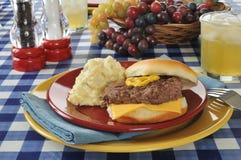 Cheeseburger and potato salad Royalty Free Stock Images