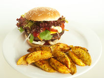 Cheeseburger with potato wedges. On plate; green and white striped tablecloth, tomatoes as decoration Royalty Free Stock Photos