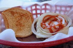 Cheeseburger. A cheeseburger with raw onions and ketchup on a toasted bun royalty free stock images
