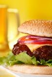 Cheeseburger sabroso con la pinta de cerveza en fondo Fotos de archivo libres de regalías