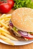 Cheeseburger sabroso con las fritadas Foto de archivo