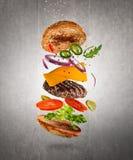 Cheeseburger sabroso con los ingredientes del vuelo en fondo oscuro fotografía de archivo