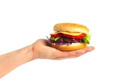 Cheeseburger sabroso en la mano femenina Imágenes de archivo libres de regalías