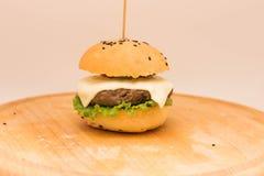 Cheeseburger sabroso en un tablero de madera Imagen de archivo libre de regalías
