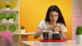 Cheeseburger sabroso penetrante femenino hermoso, fondo de la tabla de la limpieza de la camarera almacen de metraje de vídeo