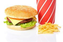 Cheeseburger, soda drinks and french fries. Reflected on white background. Shallow DOF Stock Image