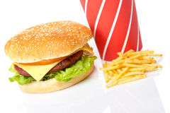 Cheeseburger, soda drinks and french fries. Reflected on white background. Shallow DOF Stock Photos
