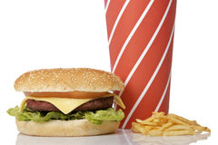 Cheeseburger, soda drinks and french fries. Reflected on white background. Shallow depth of field Royalty Free Stock Images