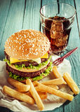 Cheeseburger, soda and French fries. Double-decker beef cheeseburger on a sesame bun, soda and French fries served as a takeaway snack on crumpled paper on a Stock Images