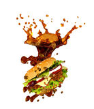 Cheeseburger splashing in cola Stock Photography