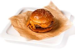 Cheeseburger sur le papier de cuisson dans un plat blanc sur un fond blanc d'isolement photos libres de droits