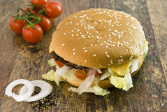 Cheeseburger Tomato and Oniond. Cheeseburger with Tomato and Onion lying on wood stock image
