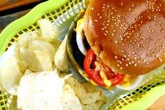 Cheeseburger und Kartoffelchips Stockfotos