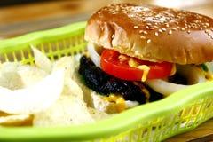 Cheeseburger und Kartoffelchips Lizenzfreie Stockbilder