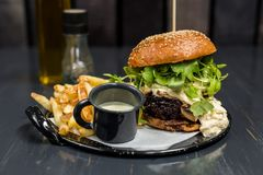 Cheeseburger with vegetables, garlic sauce and french fries on a wooden table stock image