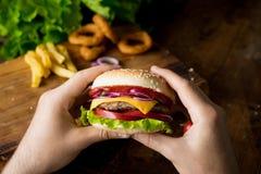 Cheeseburger w rękach Obrazy Royalty Free