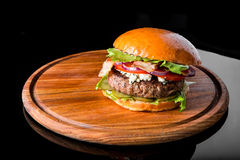 Cheeseburger on a wooden board Stock Image