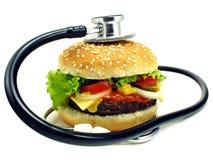 Cheeseburger y estetoscopio imagenes de archivo