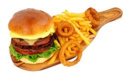 Cheeseburger y fritadas con los anillos de cebolla foto de archivo