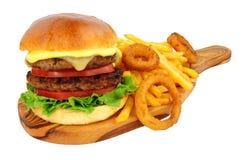 Cheeseburger y fritadas con los anillos de cebolla imagen de archivo libre de regalías
