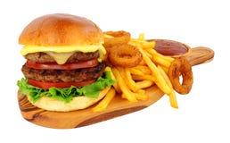 Cheeseburger y fritadas con los anillos de cebolla fotografía de archivo libre de regalías