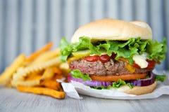 Cheeseburger y patatas fritas Imagen de archivo libre de regalías