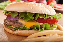 Cheeseburger y patatas fritas con los ingredientes Fotografía de archivo