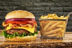 Cheeseburger z bekonem i koszem francuscy dłoniaki zdjęcie stock