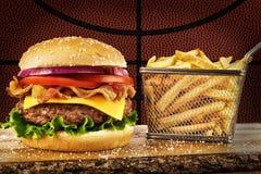 Cheeseburger z bekonem i koszem francuscy dłoniaki fotografia stock