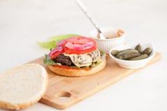 Cheeseburger z cutlet i rozciekłym serem z zalewami obraz stock