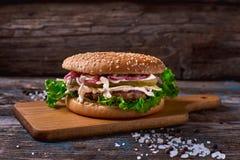 Cheeseburger z mięsnym cutlet i kiszonym warzywem na drewnianej tnącej desce na Nieociosanej Drewnianej powierzchni z Ciemnym tłe Fotografia Royalty Free