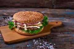 Cheeseburger z mięsnym cutlet i kiszonym warzywem na drewnianej tnącej desce na Nieociosanej Drewnianej powierzchni z Ciemnym tłe Fotografia Stock
