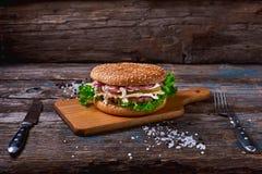 Cheeseburger z mięsnym cutlet i kiszonym warzywem na drewnianej tnącej desce na Nieociosanej Drewnianej powierzchni z Ciemnym tłe Obraz Stock
