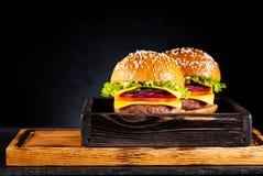 2 cheeseburgers бургеров с котлетой, сыром и овощами Стоковое Изображение RF