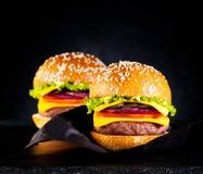 Cheeseburgers бургеров с котлетой, сыром и овощами Стоковые Изображения