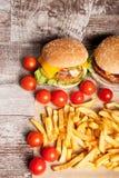 Cheeseburgers и фраи француза на деревянной плите Стоковое Изображение