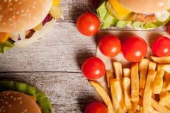 Cheeseburgers и фраи француза на деревянной плите Стоковые Изображения