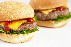2 cheeseburgers на деревянной таблице Стоковая Фотография RF