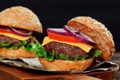 Cheeseburgers на деревянном столе с космосом экземпляра Стоковые Изображения RF