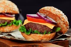 Cheeseburgers на деревянном столе с космосом экземпляра Стоковые Изображения