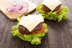 Cheeseburgers на плюшках с суккулентной говядиной на деревянном столе Стоковое Фото
