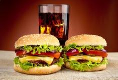 2 cheeseburgers, стекло колы на деревянном столе на красной фаре Стоковые Изображения