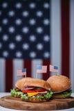 3 cheeseburgers с маленькими американскими флагами на деревянной доске, нами флаг на предпосылке Стоковая Фотография