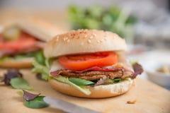 Cheeseburgers с салатом arugula на таблице Стоковые Изображения RF
