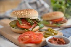 Cheeseburgers с салатом arugula на таблице Стоковая Фотография RF