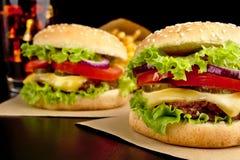 Cheeseburgers, фраи француза и кола на деревянном столе на черноте Стоковые Фотографии RF