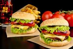 Cheeseburgers, французы жарят на деревянном столе на черноте Стоковое Фото