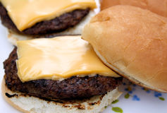 Cheeseburgers. Barbecued burgers with melted cheese on a toasted bun royalty free stock image