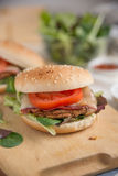 Cheeseburgers with arugula salad on a table Royalty Free Stock Photos