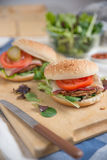 Cheeseburgers with arugula salad on a table Stock Photography